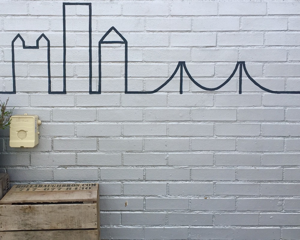 simple line painting on brick of downtown Pittsburgh buildings and bridge