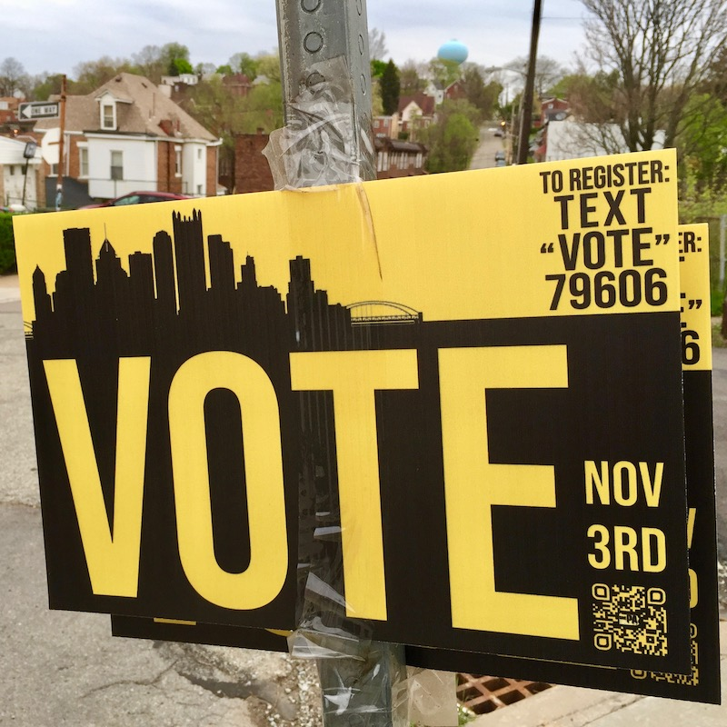 pro-vote sign taped to street sign