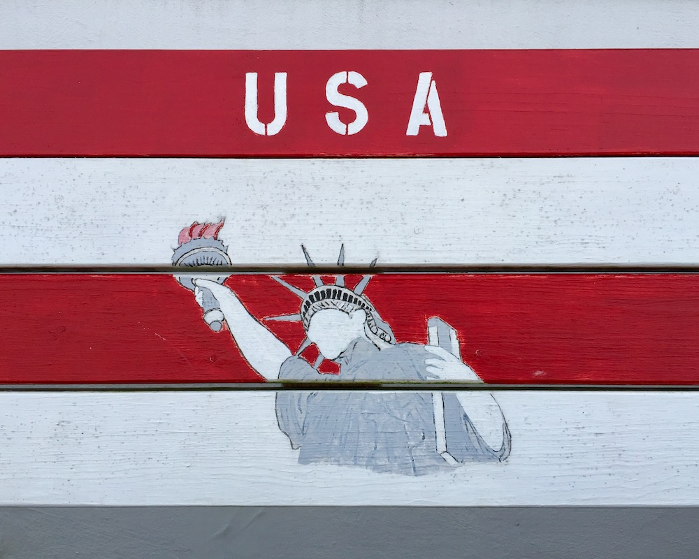 """detail of wooden bench painted with red and white stripes, Statue of Liberty, and """"USA"""""""