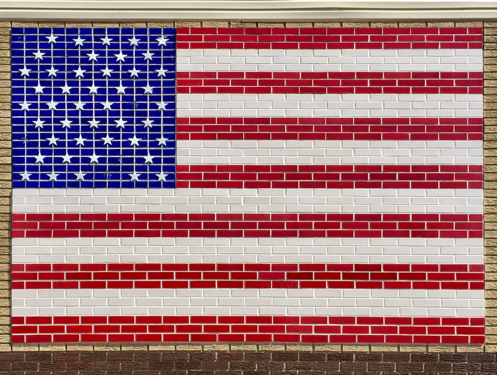 brick wall with inlaid tile to look like American flag