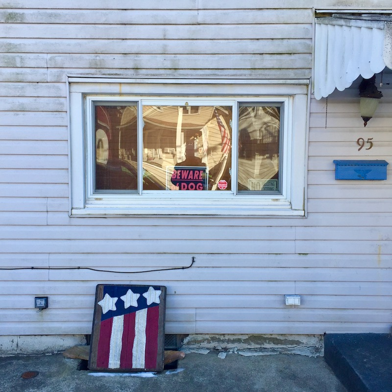 row house with wooden window cover painted like the American flag