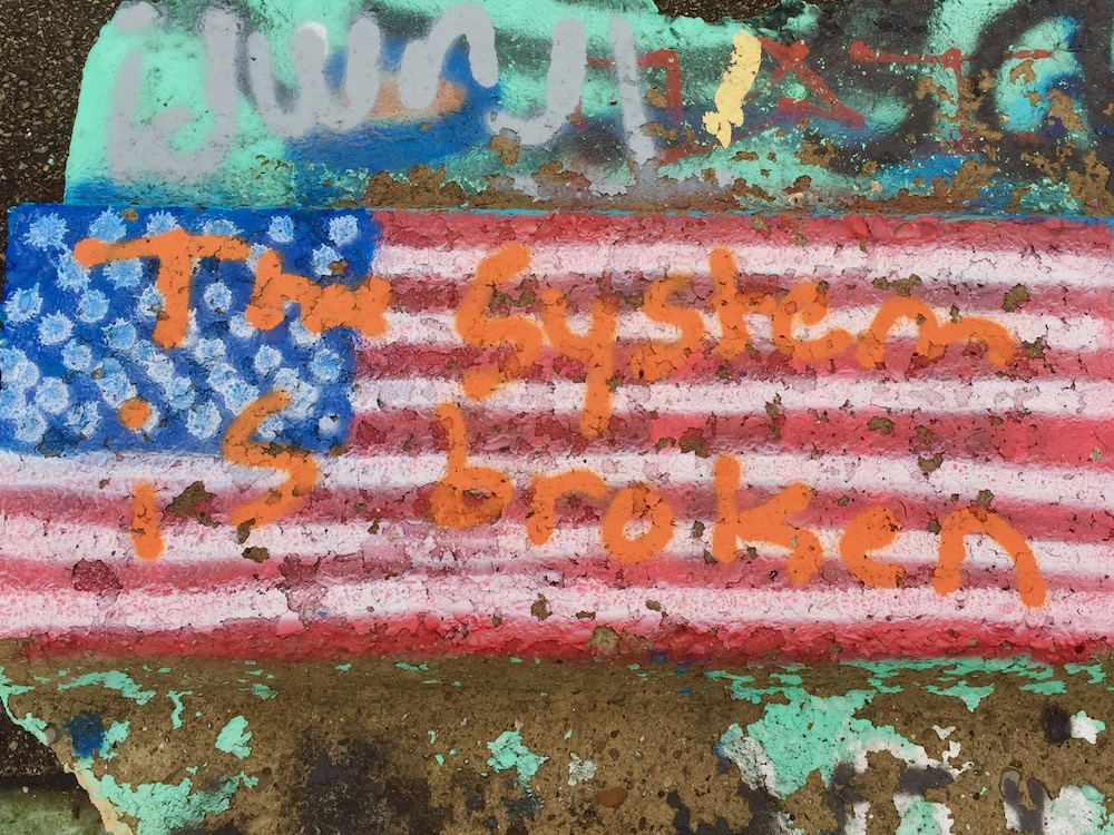 """spray-painted American flag with the text """"The system is broken"""""""
