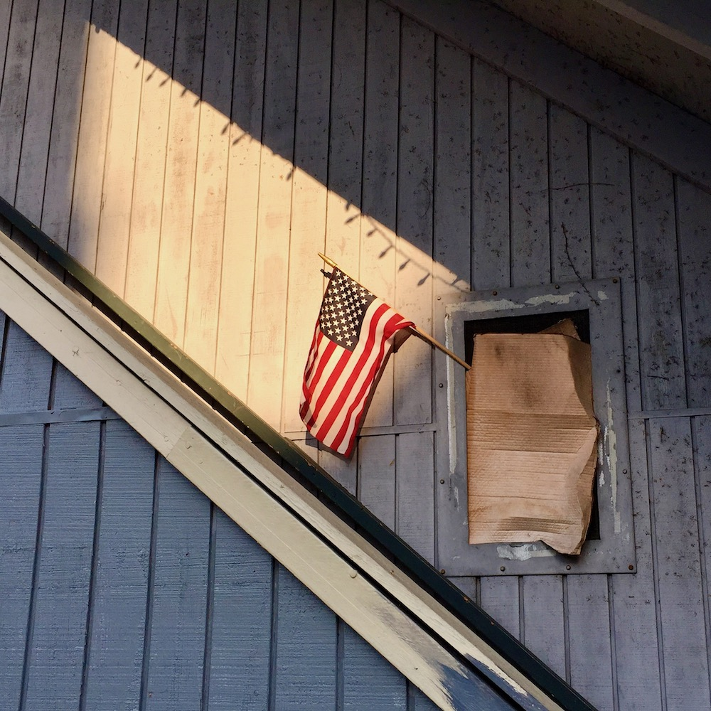 small window covered in cardboard with American flag sticking out