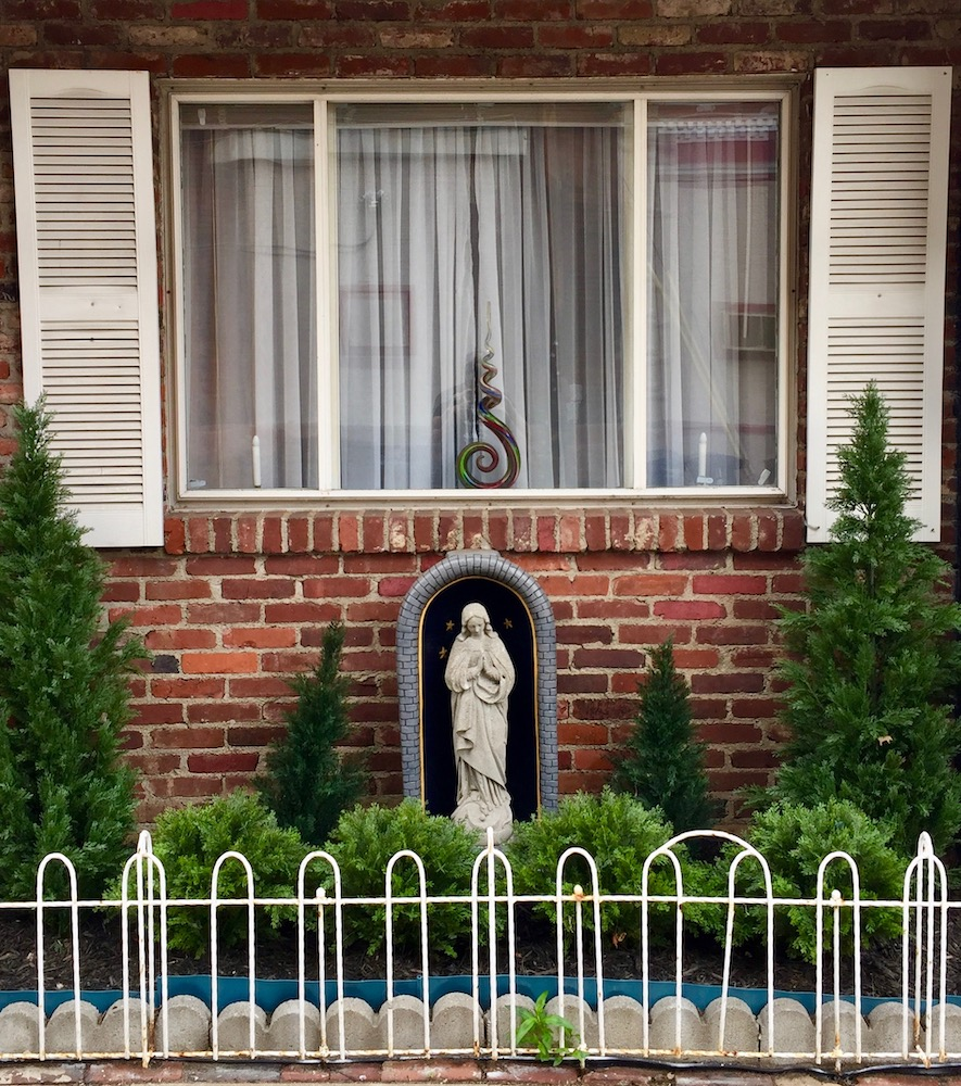 statue of Mary in front of brick house