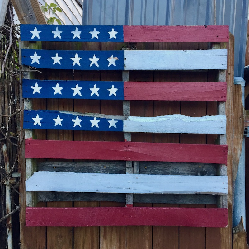 shipping pallet painted like the American flag, hung on alley fence