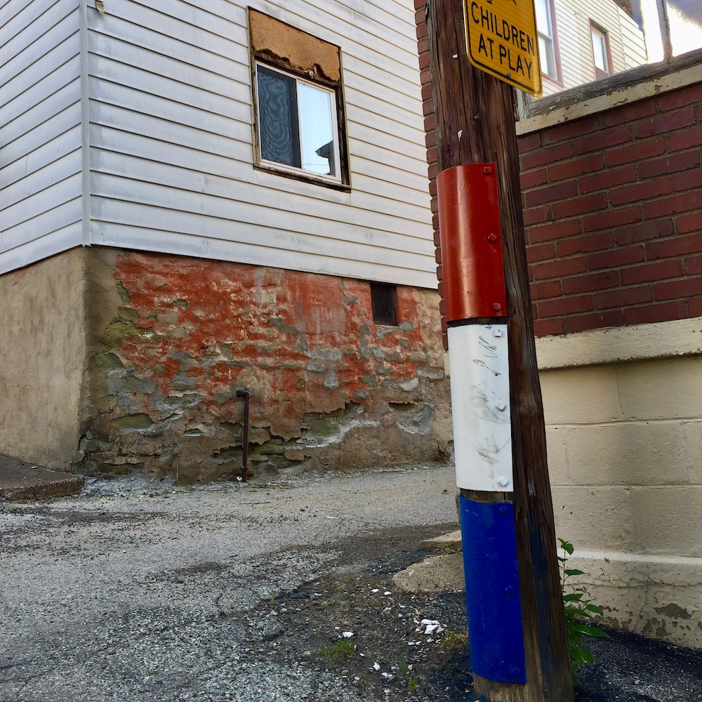metal protective plates on alley utility pole painted red, white, and blue