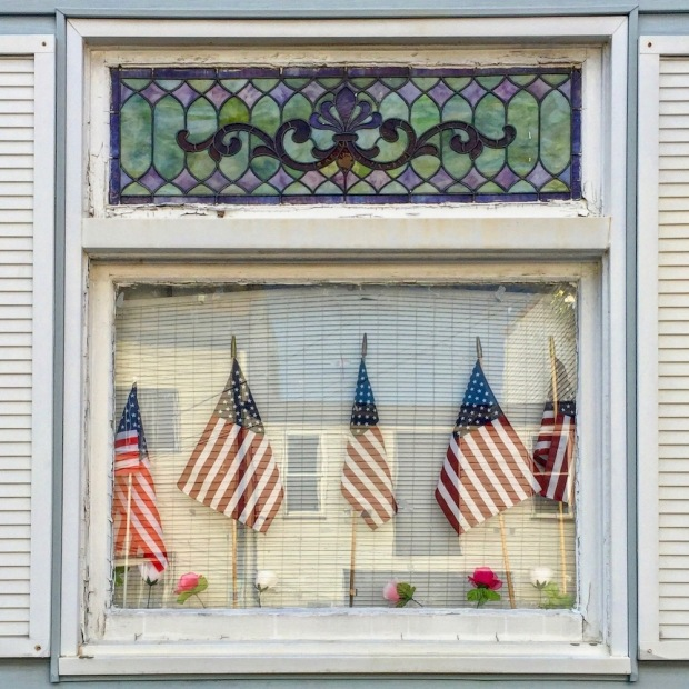 row house window decorated with multiple American flags