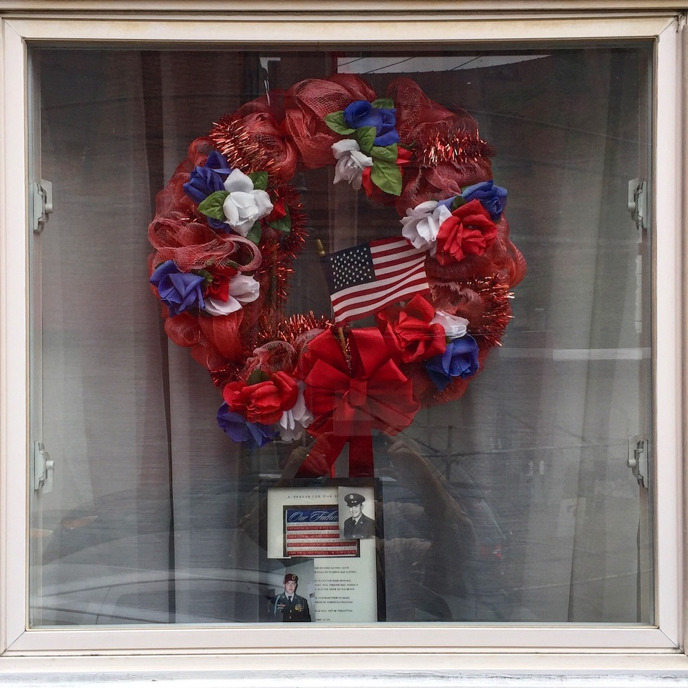 window decoration of red, white, and blue wreath and American flag