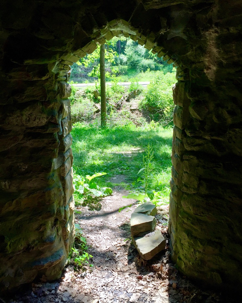 view through stone doorway to sunny wooded area