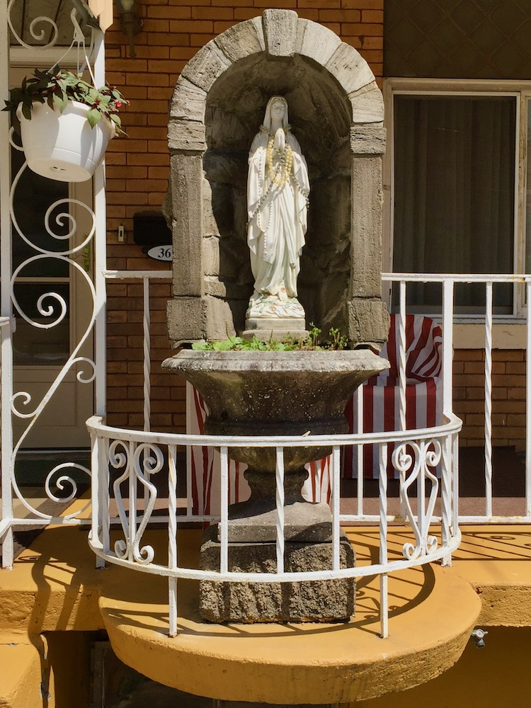 statue of Mary in grotto enclosure on pedestal in special attachment to front porch