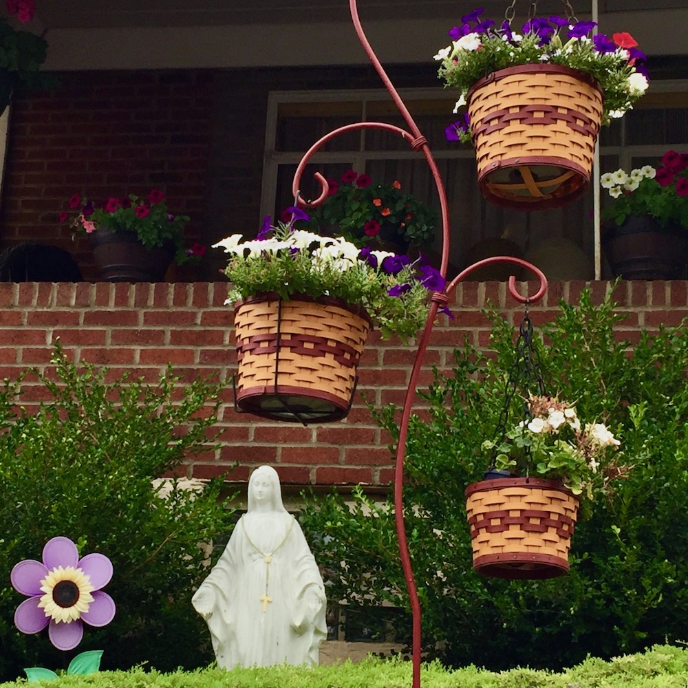 statue of Mary in front of brick house with hanging flower baskets