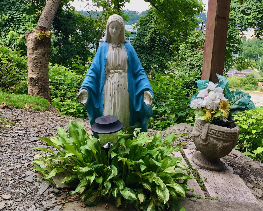 statue of Mary behind small hosta plant with solar light