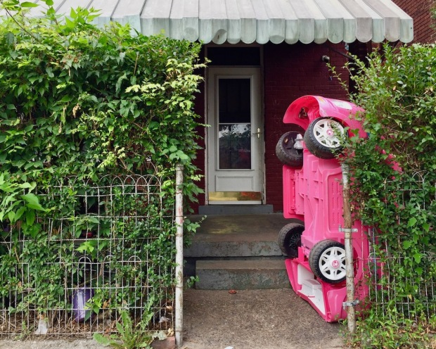 large pink toy car parked vertically in front of brick house