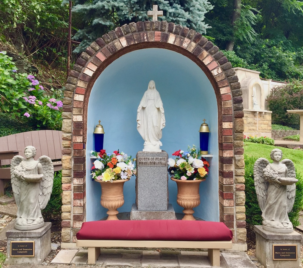ornate shrine to Mary including large brick and masonry grotto, statue of Mary on a stone pedestal, urns with flowers, candles, and angel statues