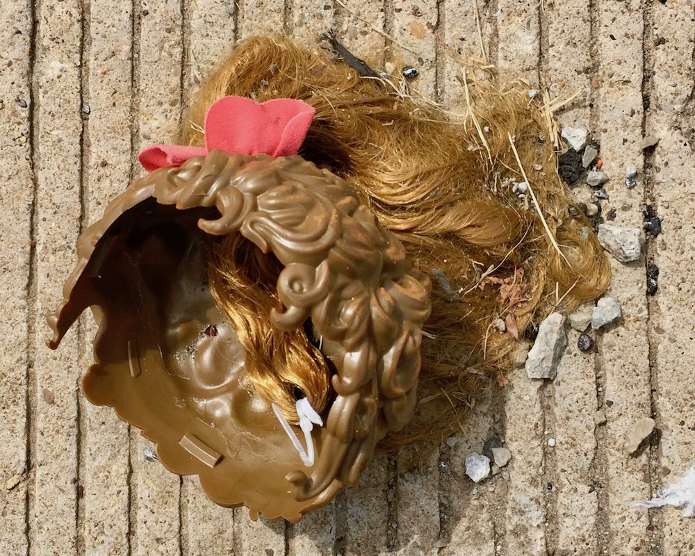 plastic doll's hairdo with attached hair found on roadside