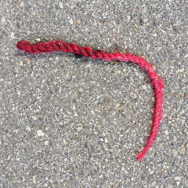 dyed red hair braid on road surface