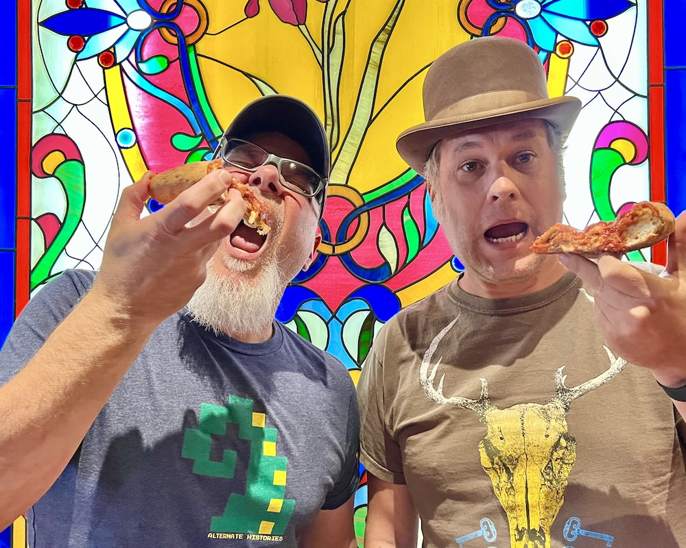 two men holding slices of pizza in front of a stained-glass window