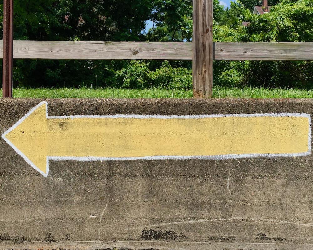 long yellow arrow painted on masonry wall