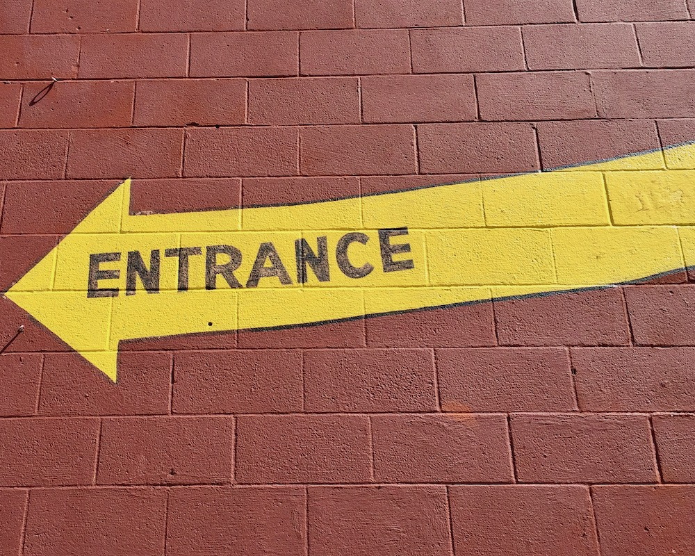 """yellow arrow with word """"Entrance"""" painted on it on cinderblock wall"""