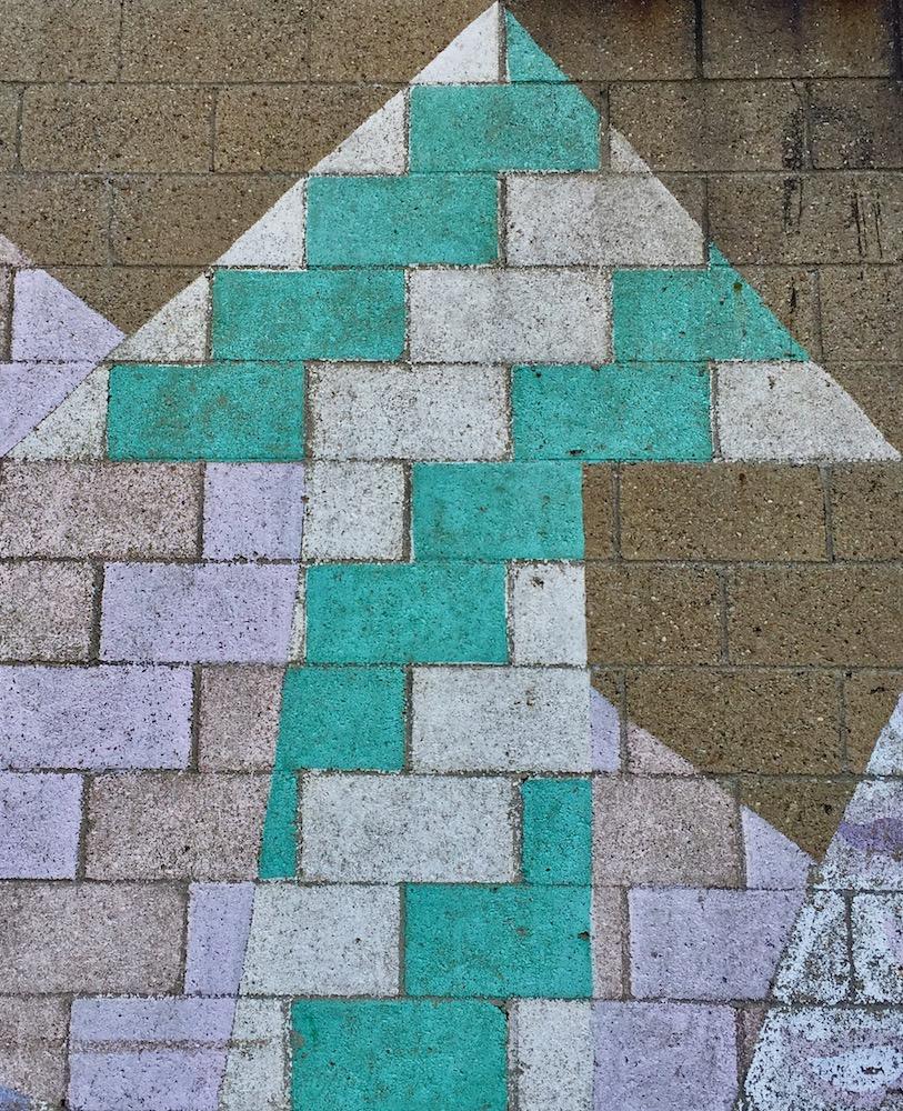 multicolor arrow painted on cinderblock wall