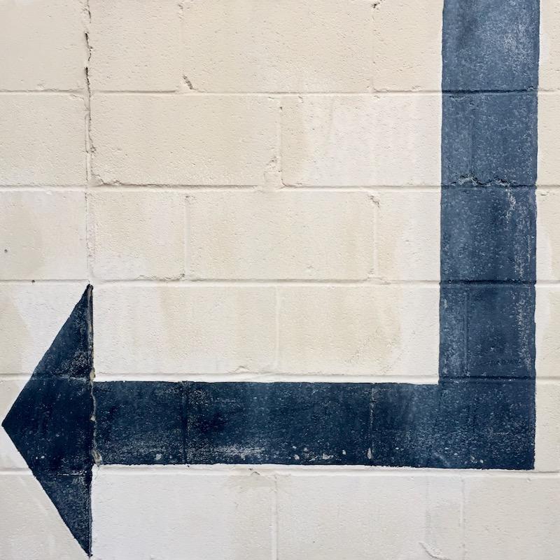 black arrow painted on white cinderblock wall