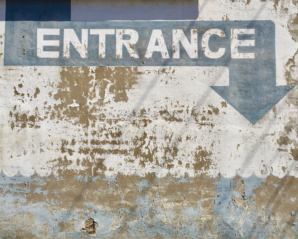 """old masonry wall with blue arrow with the word """"Entrance"""""""