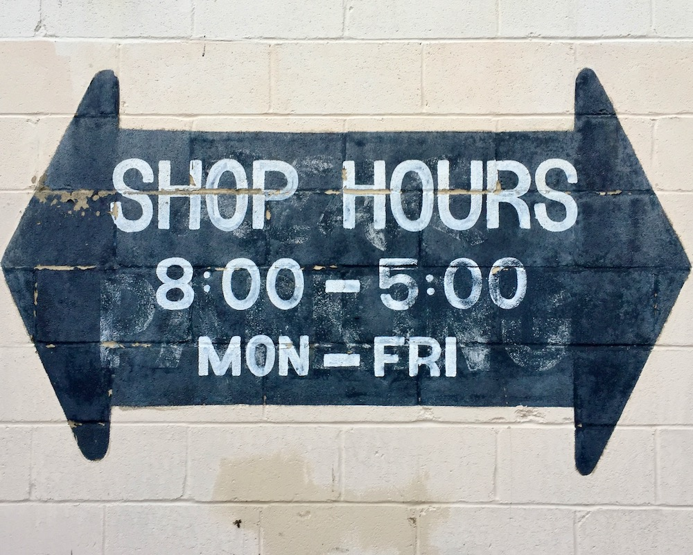 arrow with two heads pointed opposite directions and shop hours listed