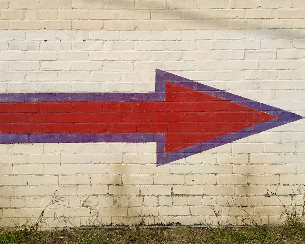 red and purple arrow painted on white brick wall