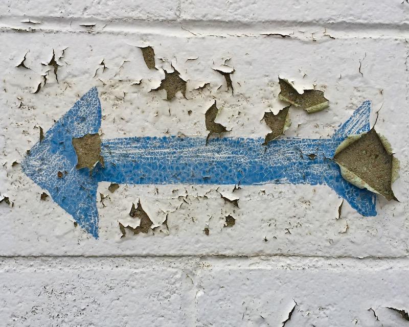 blue arrow painted on peeling cinderblock wall