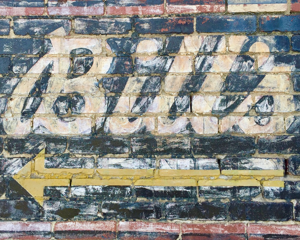 ghost sign for Bill's bar painted on brick wall
