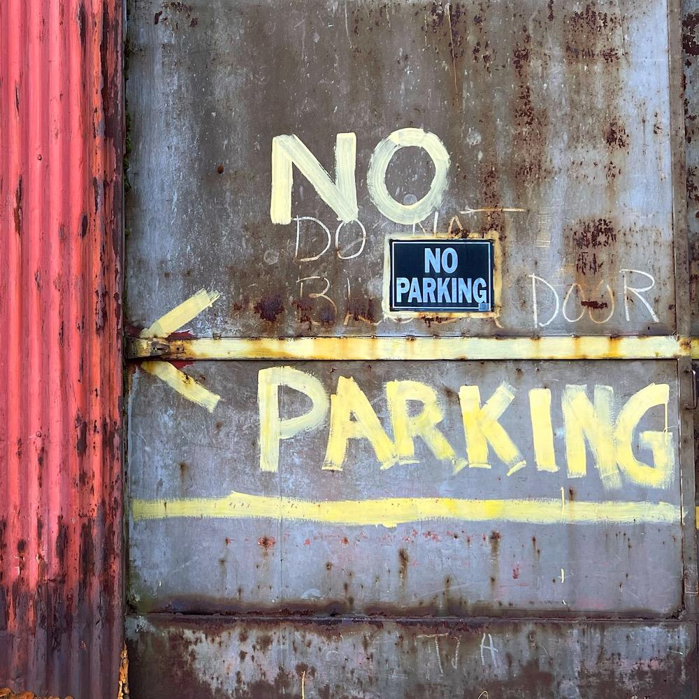"""steel door painted with """"no parking"""" and arrow"""