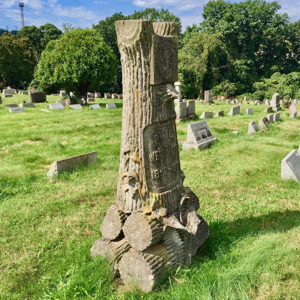 Woodmen of the World grave monument carved to look like a tree trunk on a base of cut logs